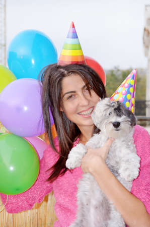 happy young woman celebrating birthday with her dog with balloons and hats Stock Photo