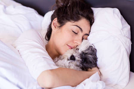 beautiful young  woman sleeping with her small poodle dog in a bed