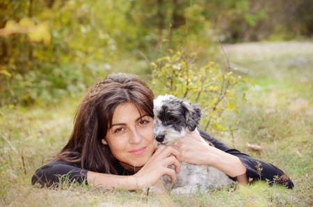 havanese: smiling woman laying on a meadow with her small havanese dog