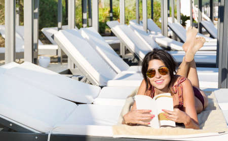 young beautiful woman relaxing and reading a book on the beach .Summer holiday