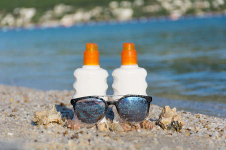 two bottles of sunscreen with shell and sunglasses on the  beach.summer sunbath - suntan oil Stock Photo