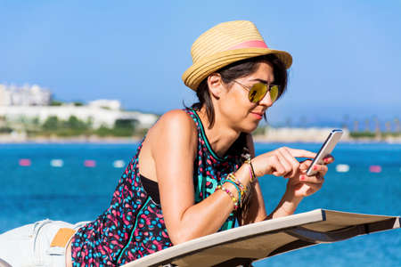 Portrait of Beautiful  Woman Using Mobile Phone on the Beach