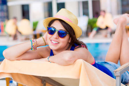 beautiful young woman relaxing on a sunbed on a pool background.Summer holiday