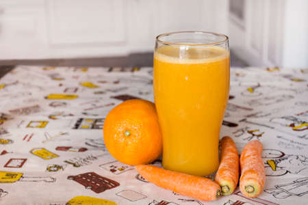 A glass of orange and carrots smoothie . Healthy life concept.