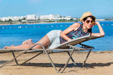 beautiful young woman relaxing on a sunbed on a sea background.Summer holiday