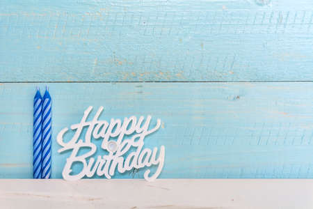 blue birthday candles isolated on a blue  wooden background