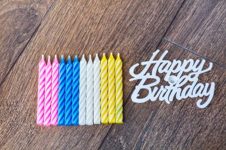 birthday candles and happy birthday sign isolated on a wooden background Stock Photo