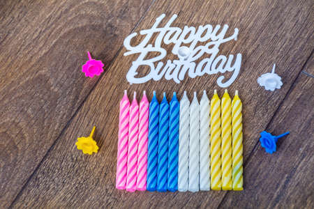 birthday candles and happy birthday sign isolated on a wooden background Banco de Imagens