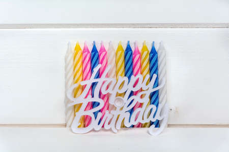 Set of colored birthday candles and happy birthday sign  on a white wooden background