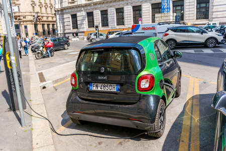 MILAN, ITALY - JUNE 27,2018: Charging Modern Electric Small Smart Car on the Street . Eco Car