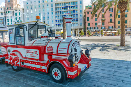 GENOA,ITALY:JUNE 24,2018 : Red City Tour Shuttle Train .Tourist Train with Tourists Discovering the  City Attractions Editorial