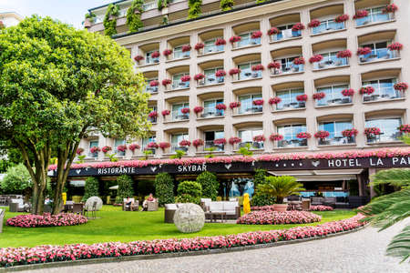 STRESA,LAKE MAGGIORE,ITALY-JUNE 25,2018 : Grand Hotel Des Iles Borromees with Windows with Geranium Flowers Blooming Abundantly Editorial