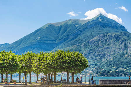 COMO LAKEITALY-JUNE 27,2018 :Lago di Como in Italy with Green Trees in a Row and Mountain Hills in the Background