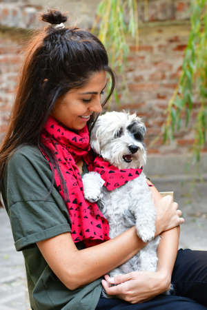 Beautiful Smiling Woman Hugging  Her Cute Havanese  Dog on the Street.Pet and Owner Outdoor in the City