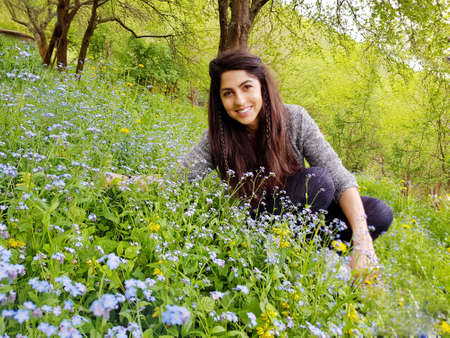 Beautiful Young Smiling Woman in a Blooming Spring Green  Garden Zdjęcie Seryjne