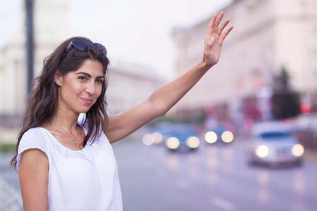 Young Woman Hailing a Taxi on the Street Zdjęcie Seryjne