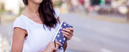 Young Woman with Wallet in the Hands on the Street. Unrecognizable People