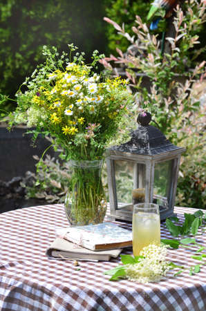 Elderberry Lemonade on a Table with Bouquet of Wild Flowers and Wooden Lantern