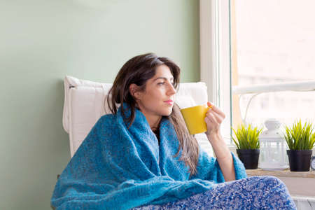 Beautiful Young Woman Staying at Home ,Looking  through the Window with Cup of Coffee in the Hands