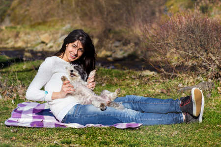 Happy Woman Hugging  Her Cute Dog in the Nature .Pet and Owner Outdoor
