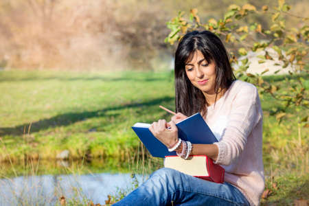 Beautiful Woman Studying Outdoor on a Lake Background