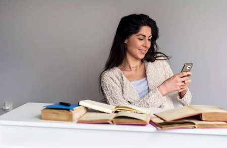 Happy Young Woman Studying at Home Reading a Text Message on her Mobile Phone .Online Learning Zdjęcie Seryjne