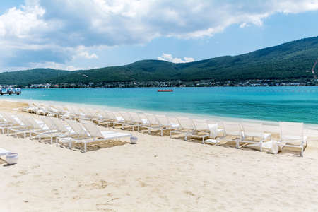 Sunbeds on Sandy Beach with Azure Sea and Mountain View in Turkey