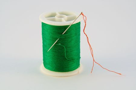 A Green Spool of Thread armed with a needle left over from a red thread repair