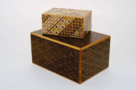 two Japanese puzzle boxes made from various inlaid woods