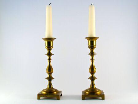 ペアとして立っている白い燃やされた蝋燭と 2 つの真鍮の燭台 写真素材