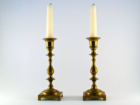 Two brass candelabras with white burned candles standing as a pair