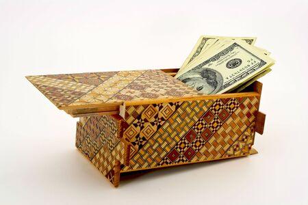 Hundred dollar bills hidden in an open japanese puzzle box Banco de Imagens