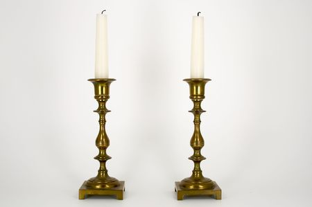 Two Brass Candelabras with white candles with burned wickes