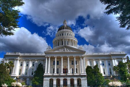 state government: an HDR image of the California State Capital Building from a distance bordered by trees and a blue sky with grey and white clouds