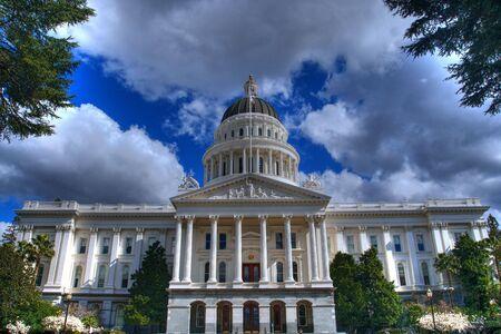 Une image HDR du California State Capital Building d'une distance bordée d'arbres et d'un ciel bleu avec des nuages gris et blancs Banque d'images - 4458156