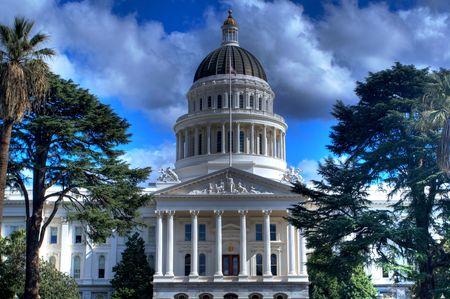 hdr: une image HDR du b�timent de la Californie capitale du Land de loin, bord� d'arbres et un ciel bleu avec des nuages gris et blanc Banque d'images