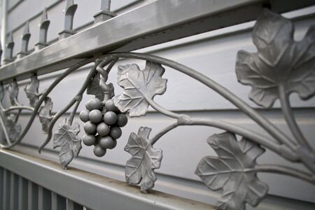 oblique view of grey wroght iron gate with a design og grapes and grape leaves Stock Photo