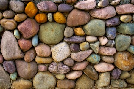 a rock wall that was made with a large variation of different colored rocks