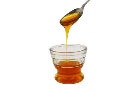 an angled spoonful of honey dripping into a partially full glass bowl Banco de Imagens