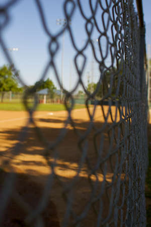 a short depth of field photo of chain link fence around a baseball field photo