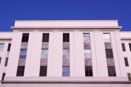 offiice: East side of the California Capical Building showing offiice windows reflecting the clouded sky