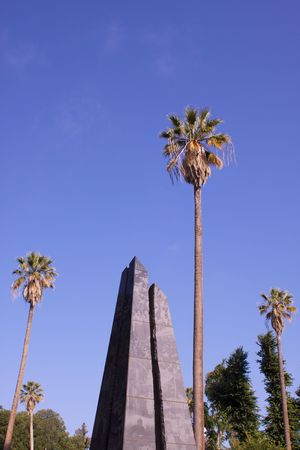 California State Park Veterans Memorial obelisk framed by Palm trees and sky photo