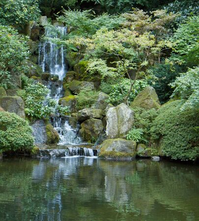 Japanese garden waterfall emptying into green pond Stock Photo - 5684087