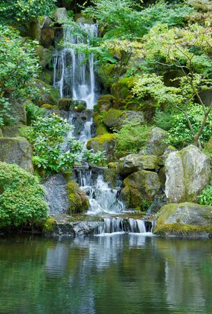 Japanese garden waterfall emptying into green pond photo