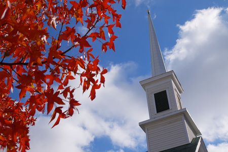 worship white: leaves that have turned red and church steeple against a blue sky Stock Photo