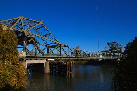 california delta: River bridge at Walnut Grove, CA in the delta of northern California framed by Bushes