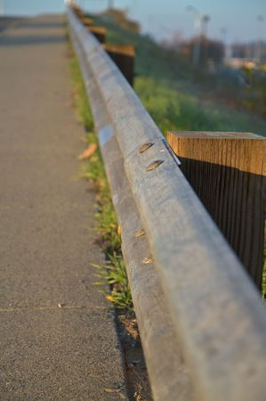 gaurd: Steel gaurd rail along road with wood posts and soft focus green hil Stock Photo