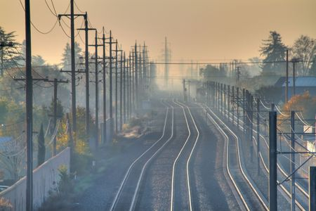 Hazy view of train tracks disappearing into the distant morning fog Banco de Imagens