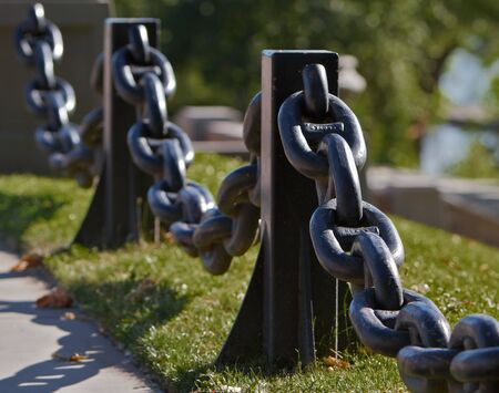 Black Steel Anchor Chain used for a railing againt grass lawn