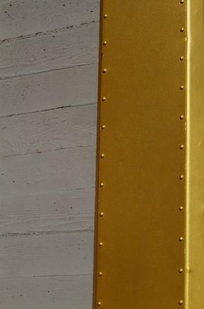 Abstract of small portion of gold beam next to concrete wall Фото со стока